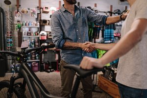 Sports shop owner selling bicycle