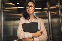 Smiling business woman in office by Jacob Lund in Business