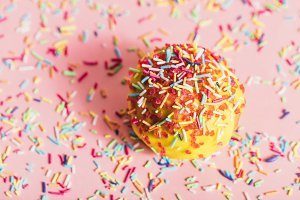 Sprinkled yellow doughnut on pink ba