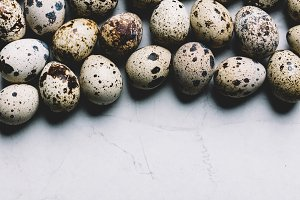 Spotted quail eggs on white marble b