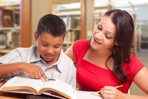 Mother Helping Son Study in Library
