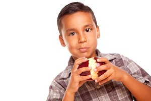 Hispanic Boy Eating A Large Apple