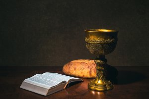 Goblet with wine bread and Bible