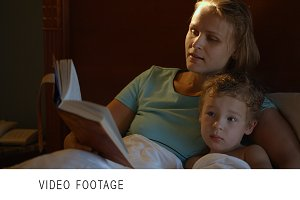 Mother and son in bed with book