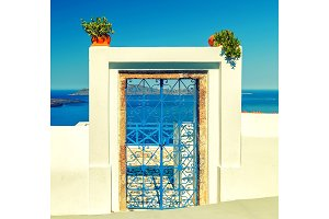 Traditional blue door on Santorini Island, Greece, with view over volcanic caldera, tonned.