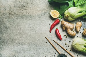 Flat-lay of Asian cuisine ingredients over grey concrete background