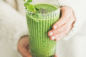 Matcha smoothie with chia seeds in female hands, square crop