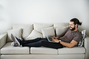 White man using laptop on sofa