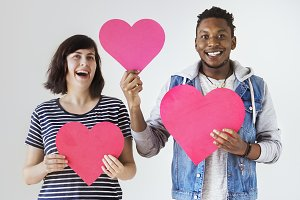 Couple holding red hearts