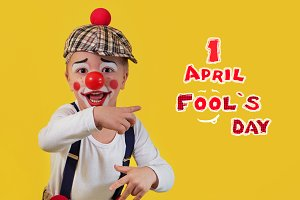 Happy clown show finger text 1 april fools day. Funny little child boy in costume, makeup, red nose cheerful clown, bright yellow background. Emotional mischievous portrait kid actor.copy space.