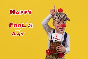 Funny child clown in a costume, makeup, red nose. Little cheerful boy jester 5 years keep box with copy space for text. 1 April fool's day celebration. Expression face joy, humor, smile, laughter.