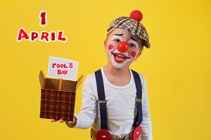 Beautiful portrait funny kid in celebration costume clown isolated on yellow background. Child clown smile keeping box. Concept birthday, day 1 april, party. Stylish emoticon jester kid 5 years.