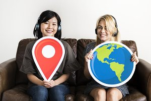 Two woman holding location icon