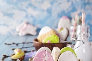 Easter cookies egg in the paper box with milk in glass on wood background