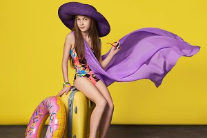Stunning girl model in a colorful bikini, hat, pareo with a suitcase. Fashion teenager woman in a swimsuit posing on a yellow background with magazine cover. Vacation, summer, concept.