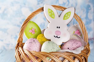 Easter cookies, bunnies and eggs in a basket on light blue background