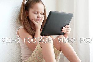 Baby little girl holding and using pc tablet and sits on the floor in room.