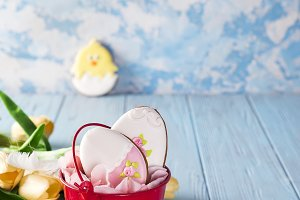 Happy Easter gingerbread cookie eggs with bucket on blue wood background,