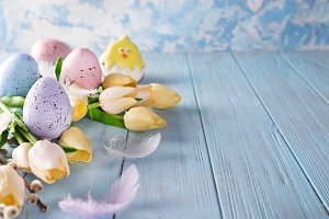 Easter colorful eggs with tulips on wood background as frame