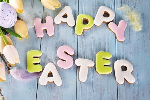 Easter cookies letter Happy Easter and colorful eggs with tulips on wood background