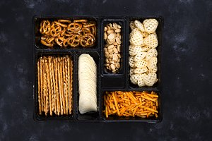 a variety of snacks on the box for beer on a concrete black table