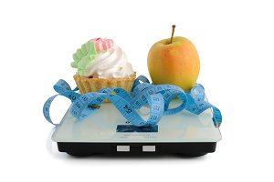 Cake and apple on scales measuring