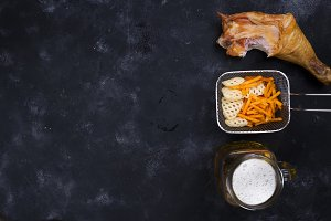 side of a glass of beer, snacks and smoked chicken leg on a black background