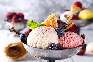 Bowl with ice cream with three different scoops of white, yellow, red colors and waffle cone, chocolate, tangerines and straws