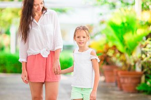 Little girl and mother walking in luxury resort on summer vacation