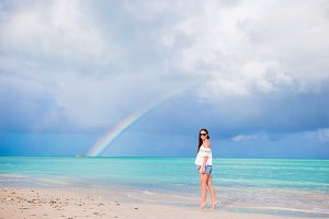 Beautiful happy woman on the beach with beautiful rainbow over the sea