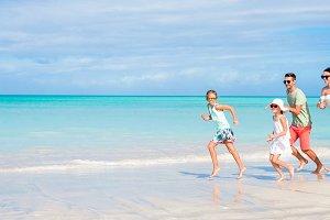 Beautiful happy family running on the seashore