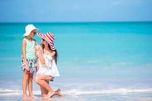 Beautiful mother and daughter at Caribbean beach enjoying summer vacation. Family walking on tropical famous Jolly bay beach