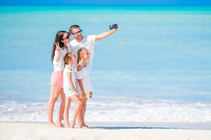 Man taking a photo of his family on the beach. Family vacation