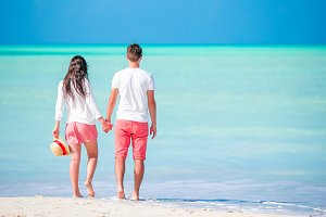 Young couple walking on tropical beach with white sand and turquoise ocean water at Antigua island in Caribbean