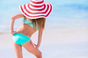 Adorable little girl in big hat walking along white sand Caribbean beach