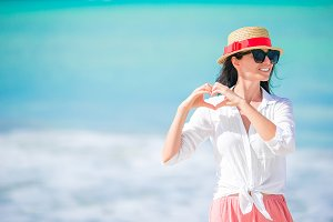 Young beautiful woman on white sand tropical beach. Caucasian girl in hat background the sea