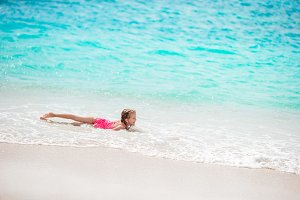 Adorable little girl at beach having a lot of fun in shallow water