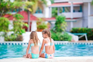 Adorable little girls in outdoor swimming pool on vacation