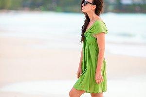 Young beautiful woman having fun on tropical seashore. Happy girl walking at white sand tropical beach