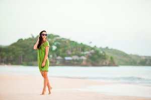 Young beautiful woman on tropical seashore. Tourist girl in green dreess on the beach