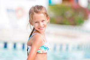 Adorable little girl relaxing at outdoor swimming pool