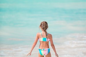 Happy little girl running and splashing at shallow water at beach having a lot of fun on vacation