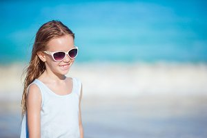 Beautiful little girl in sunglasses at beach having fun. Funny girl enjoy summer vacation.
