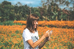 Woman taking pictures of marigold field. Bali island.