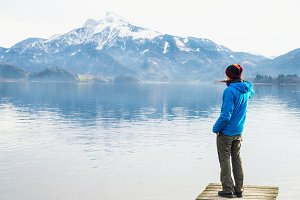 The man looking at the mirror lake and the mountains at the background with clear sky in cold weather