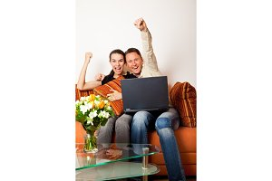 Couple Sitting On The Couch With A Laptop