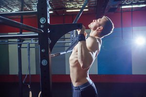 Athlete muscular fitness male model pulling up on horizontal bar in a gym. Crossfit style