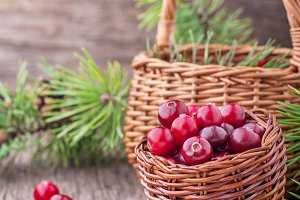 Fresh cranberries in a wicker basket on  dark wooden background