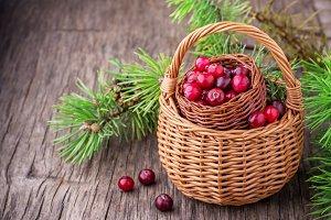 Ripe cranberries in wicker basket on dark wooden background