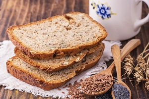 Slices of homemade dark fragrant fresh bread with poppy seeds, flax, sunflower and pumpkin